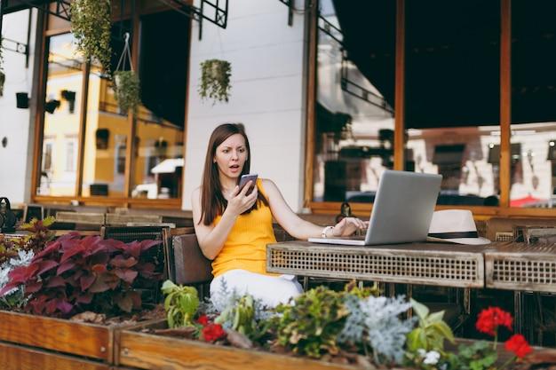 Chica triste molesta en el café de la calle al aire libre sentado con una computadora portátil, mirando en el teléfono móvil enviando mensajes de texto sms, perturbación del problema, en restaurante durante el tiempo libre