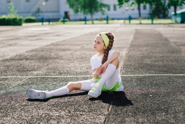 Chica trotar en una soleada tarde de verano, tendido en la caminadora, estadio, entrenamiento físico, regreso a la escuela.