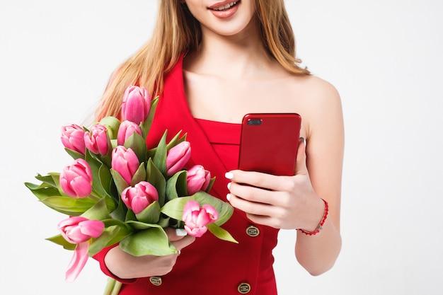 Chica con tulipanes de pie en el gris con smartphone