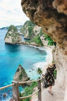 Chica turista baja las escaleras a la pintoresca playa de atuh en la isla de nusa penida, bali.