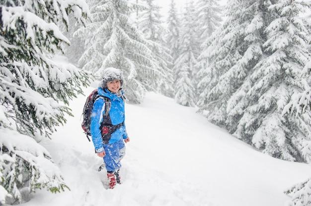 Chica turista caminando en un bosque de invierno