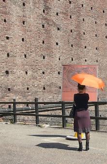 Chica turista de moda leyendo un mapa de la ciudad en milán, italia