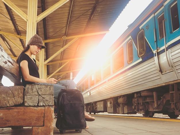 Chica turística jugando teléfono celular mientras espera el tren