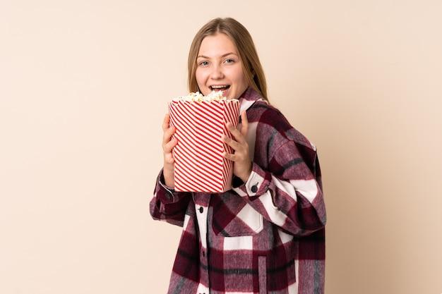 Chica ucraniana adolescente aislada en beige sosteniendo un gran cubo de palomitas de maíz