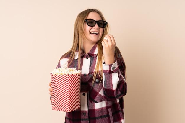 Chica ucraniana adolescente aislada en color beige con gafas 3d y sosteniendo un gran cubo de palomitas de maíz