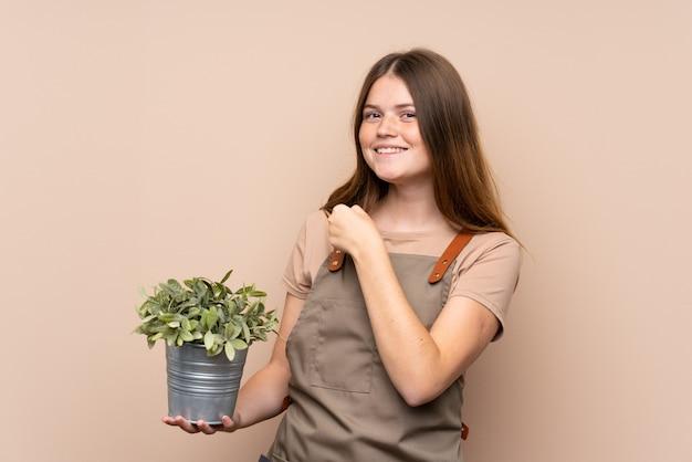 Chica ucraniana jardinero adolescente sosteniendo una planta celebrando una victoria