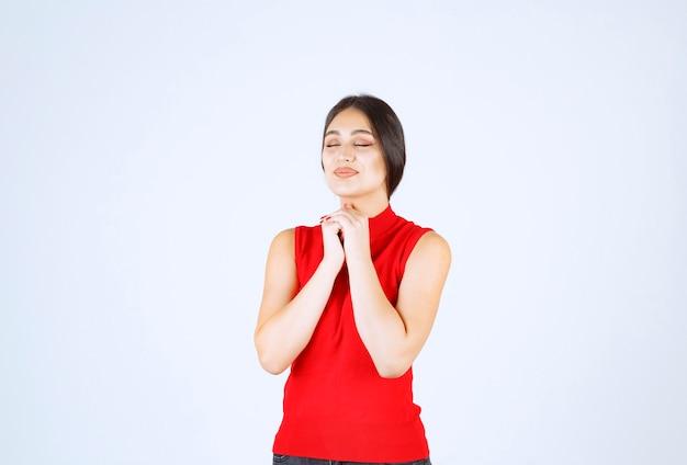 Chica uniendo sus manos y pidiendo algo.