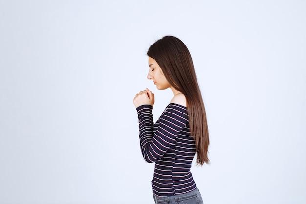 Chica uniendo sus manos y rezando.