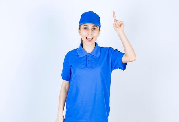 Chica en uniforme azul apuntando a algo arriba.