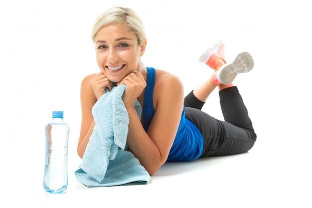 Chica en uniforme deportivo se encuentra en la estera de yoga con una toalla en blanco