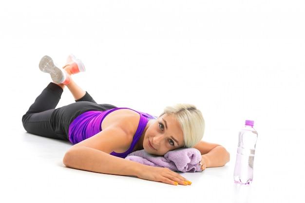 Chica en uniforme deportivo se encuentra sobre una estera de yoga con una toalla aislado fondo blanco.