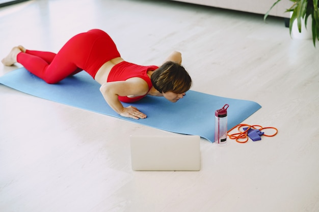 Chica en uniforme deportivo rojo practicando yoga en casa