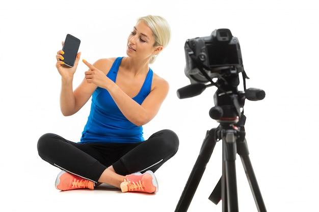 Chica en uniforme deportivo se sienta delante de la cámara en blanco