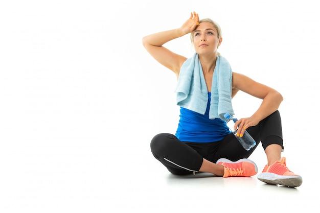 Chica en uniforme deportivo con una toalla está cansada y sentada en el suelo en blanco
