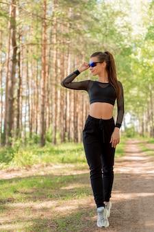 Chica en uniforme y gafas de sol haciendo deporte en un parque