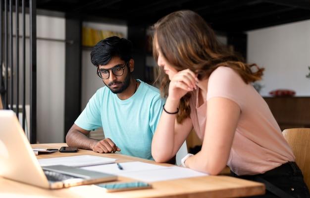 Chica universitaria y chico estudiando juntos