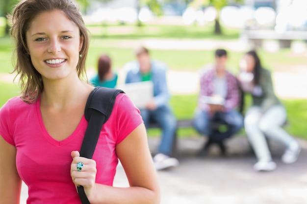 Chica universitaria sonriendo con estudiantes borrosas en el parque