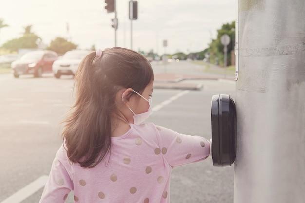Chica usando su codo presionando el botón del semáforo