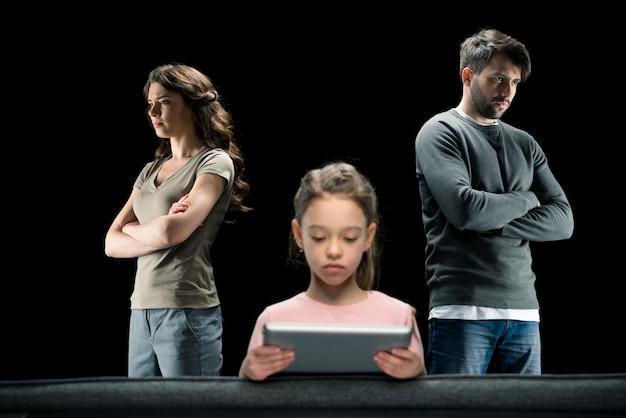 Chica usando tableta digital mientras padres de pie con los brazos cruzados sobre negro