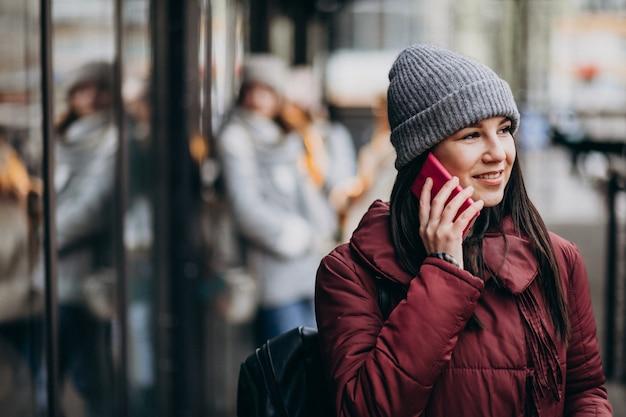 Chica usando el teléfono fuera de la calle y reuniéndose con amigos