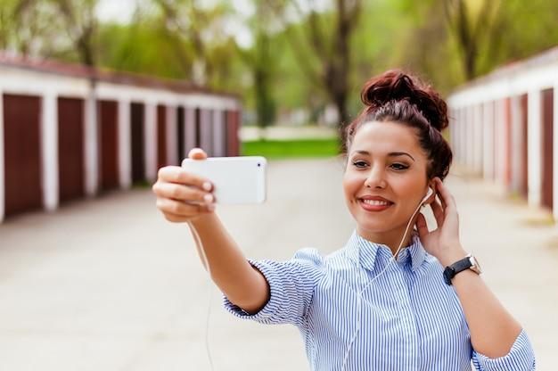 Chica usando un teléfono inteligente para conversar por video
