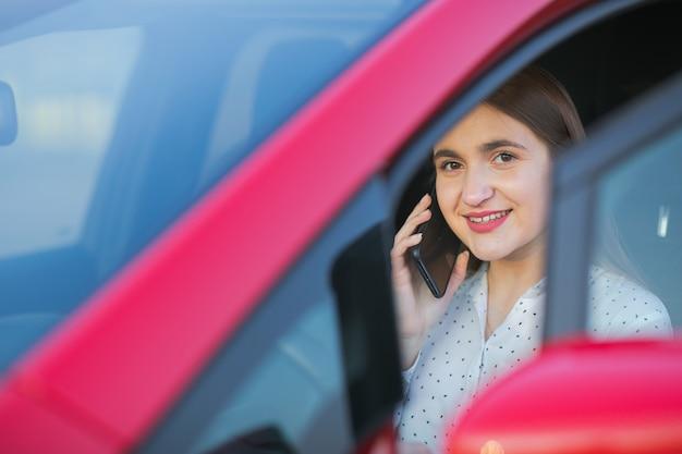 Chica usando un teléfono inteligente y esperando la fuente de alimentación se conecta a vehículos eléctricos para cargar la batería en el automóvil. chica joven positiva hablando por teléfono se sienta en el coche eléctrico y carga.