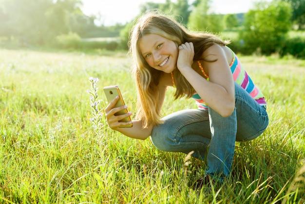 Chica usando teléfono inteligente, fotografiando flores
