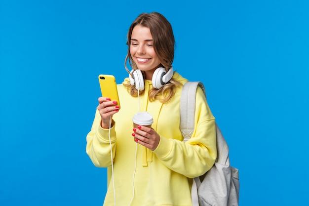 Chica usando un teléfono móvil para contactar a un amigo después de la universidad, enviando mensajes de texto mientras caminaba por la calle con una mochila, una taza de café para llevar y auriculares, sonriendo alegremente la pantalla del teléfono inteligente