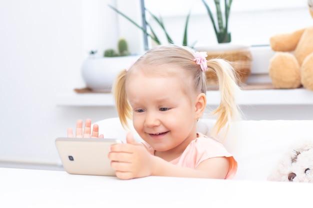 Chica usando un teléfono móvil, un teléfono inteligente para videollamadas, hablando con familiares, una niña sentada en su casa, cámara web en línea, haciendo una videollamada.