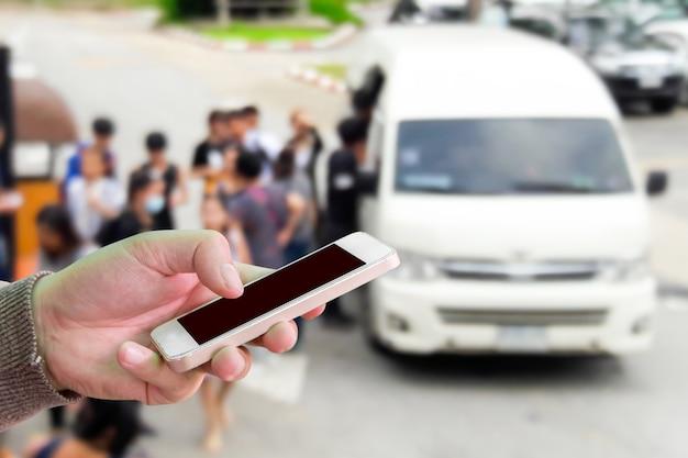 Chica uso de teléfono móvil, la imagen borrosa de furgonetas y turistas como fondo. Foto Premium