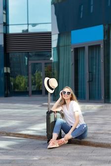 Chica de vacaciones con gafas con equipaje se sienta en el aeropuerto