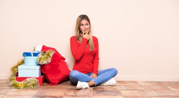 Chica en vacaciones de navidad sentada en el suelo pensando en una idea