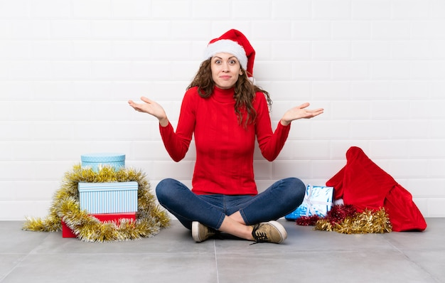 Chica en vacaciones de navidad sentados en el suelo teniendo dudas con confundir expresión de la cara