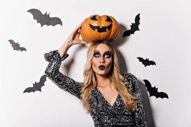 Chica vampiro de ojos azules de pie sobre una pared blanca con murciélagos. filmación en interiores de dama rubia interesada con calabaza de halloween.