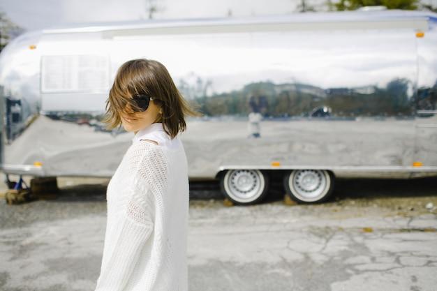 Chica vestida de blanco cerca del vehículo de lujo