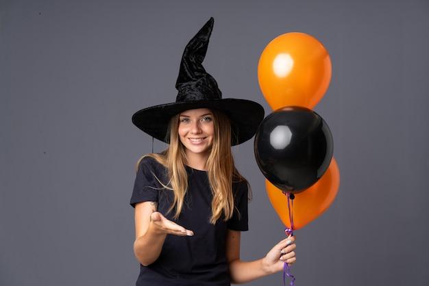 Chica vestida de bruja para halloween haciendo un trato