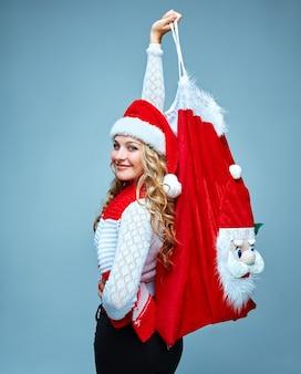 Chica vestida con gorro de papá noel sosteniendo una bolsa de decoración navideña de santa claus en azul