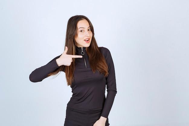 Chica vestida de negro apuntando a algo a la derecha.