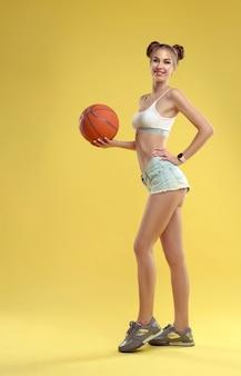 Chica vestida con pantalones cortos de jeans sosteniendo baloncesto y posando en la pared amarilla