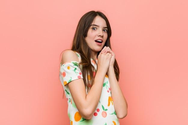 Chica vestida con una ropa de verano contra una pared asustada y asustada.