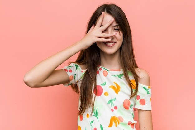Chica vestida con una ropa de verano contra una pared parpadea con los dedos, avergonzada cubriéndose la cara.