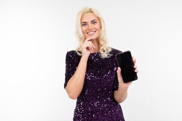 Chica en un vestido aconseja el teléfono sosteniendo la pantalla hacia adelante con el diseño para publicidad sobre un fondo blanco con espacio de copia