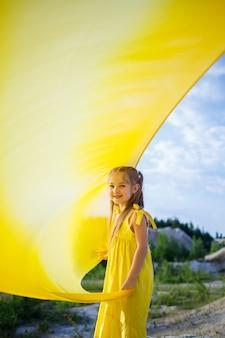 Chica con un vestido amarillo con alas en un paño amarillo cerca del lago