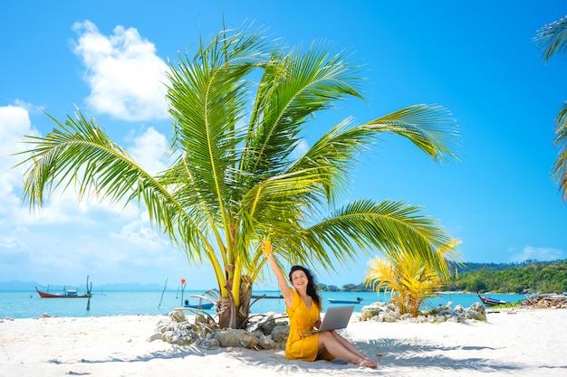 Chica con un vestido amarillo en una playa tropical de arena trabaja en una computadora portátil y bebe mango fresco. trabajo remoto, freelance exitoso. trabaja en vacaciones.
