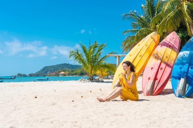 Chica con un vestido amarillo en una playa tropical de arena trabaja en una computadora portátil cerca de kayaks y bebe mango fresco. trabajo remoto, freelance exitoso. trabaja en vacaciones.