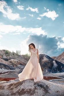 Chica en un vestido azul claro de pie en el viento con montañas