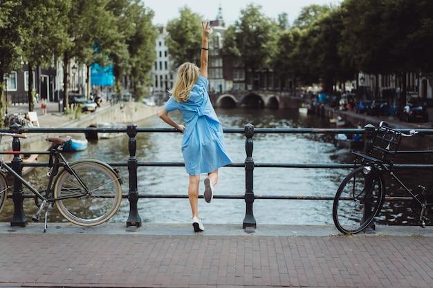 Chica en un vestido azul en el puente en amsterdam
