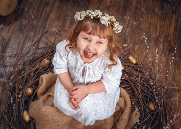 Chica con un vestido blanco con una corona de flores en la cabeza sentada en el nido