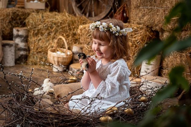 Chica con un vestido blanco con una corona de flores jugando con un pollo