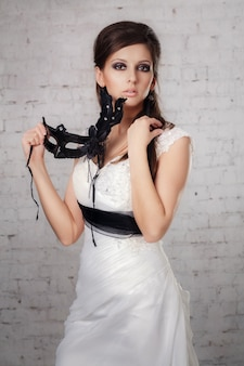 Chica con un vestido blanco con una máscara negra en studio